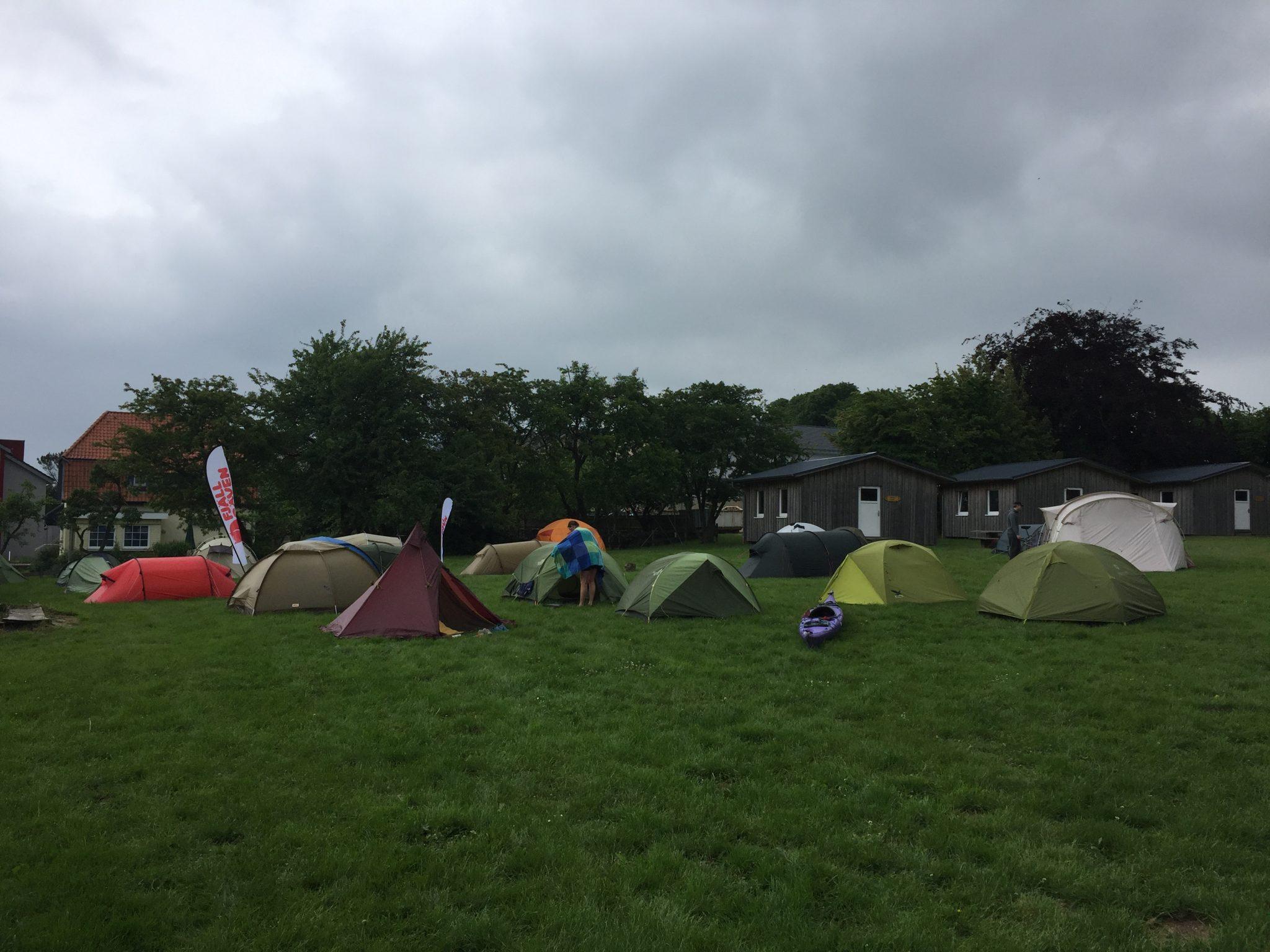 Zeltlager auf einer Wiese vor Holzhütten