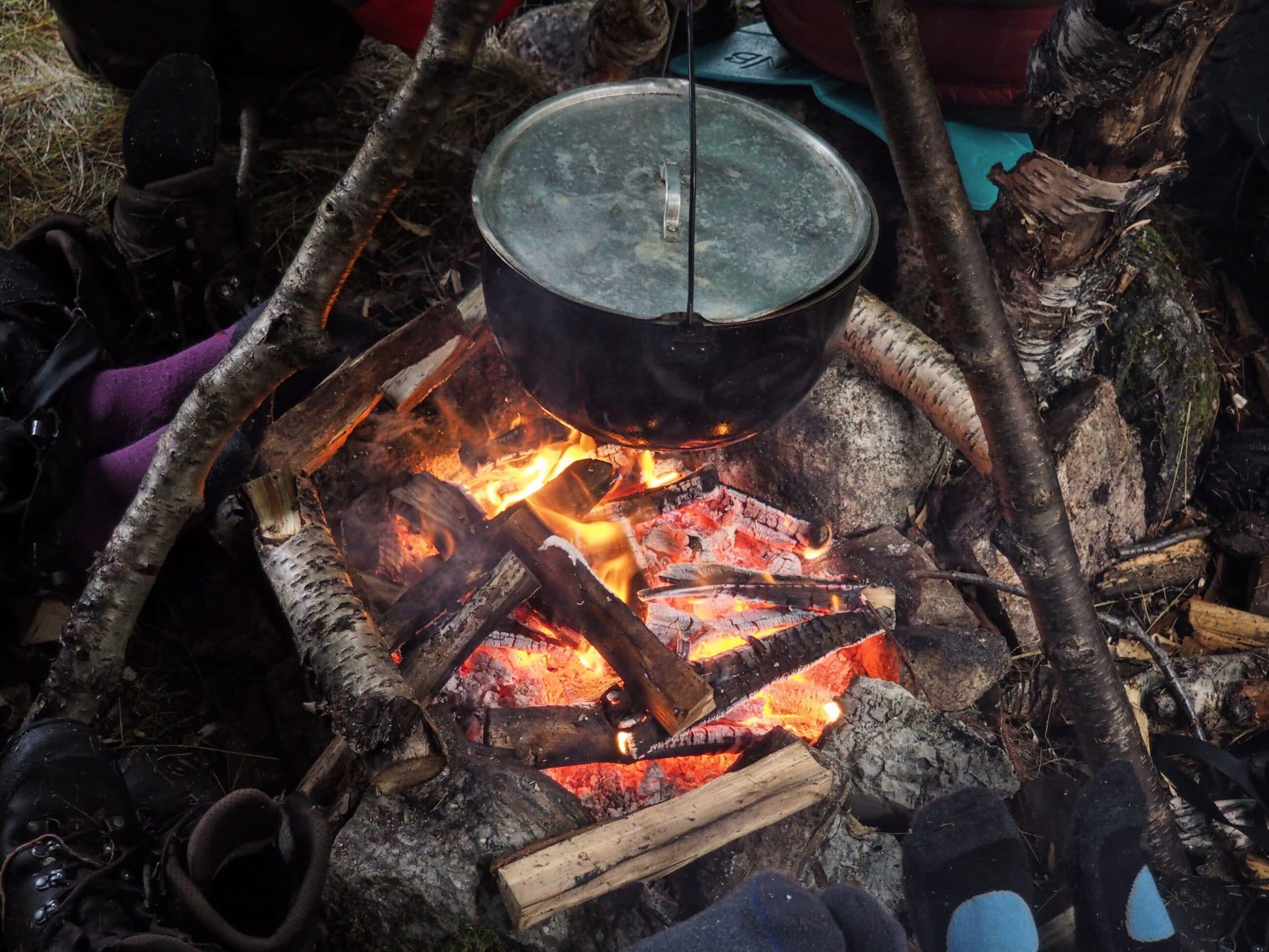 Kochtopf über offenen Lagerfeuer
